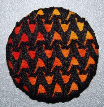 Meleret orange stof med sort elastisk blonde.