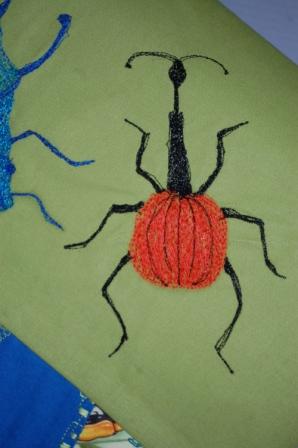 Ringbind med crazy patchwork og maskinbroderede insekter